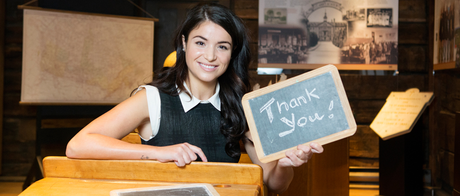 Woman holding thank-you chalkboard