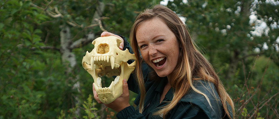 Student holding an animal skull