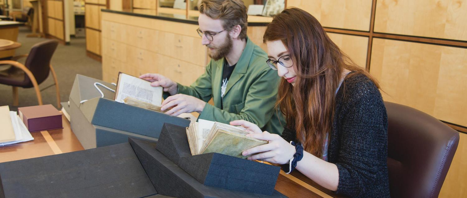 Students studying medieval manuscripts in the library