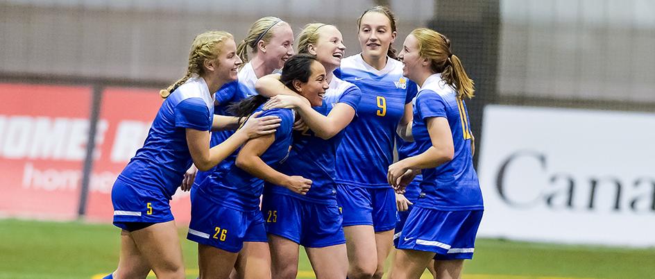 Vikes women's soccer team celebrating on the field