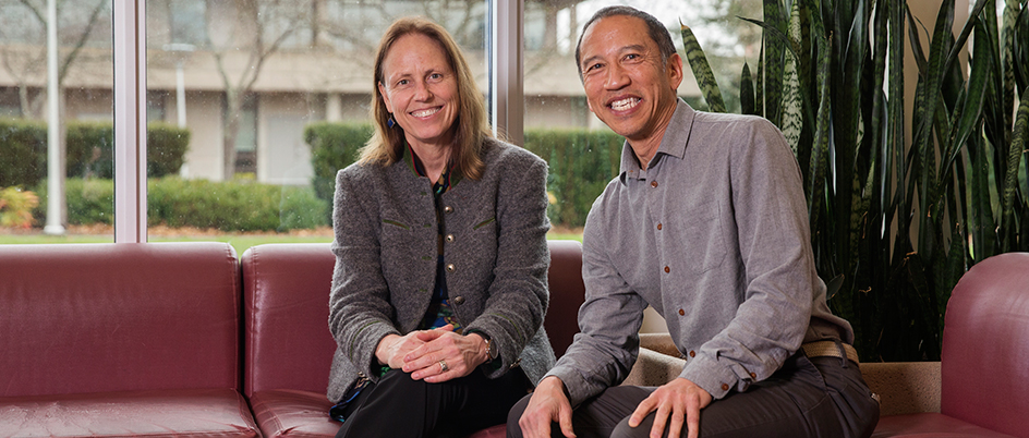 Jutta Gutberlet and Jim Tanaka sitting in a couch inside of a campus building