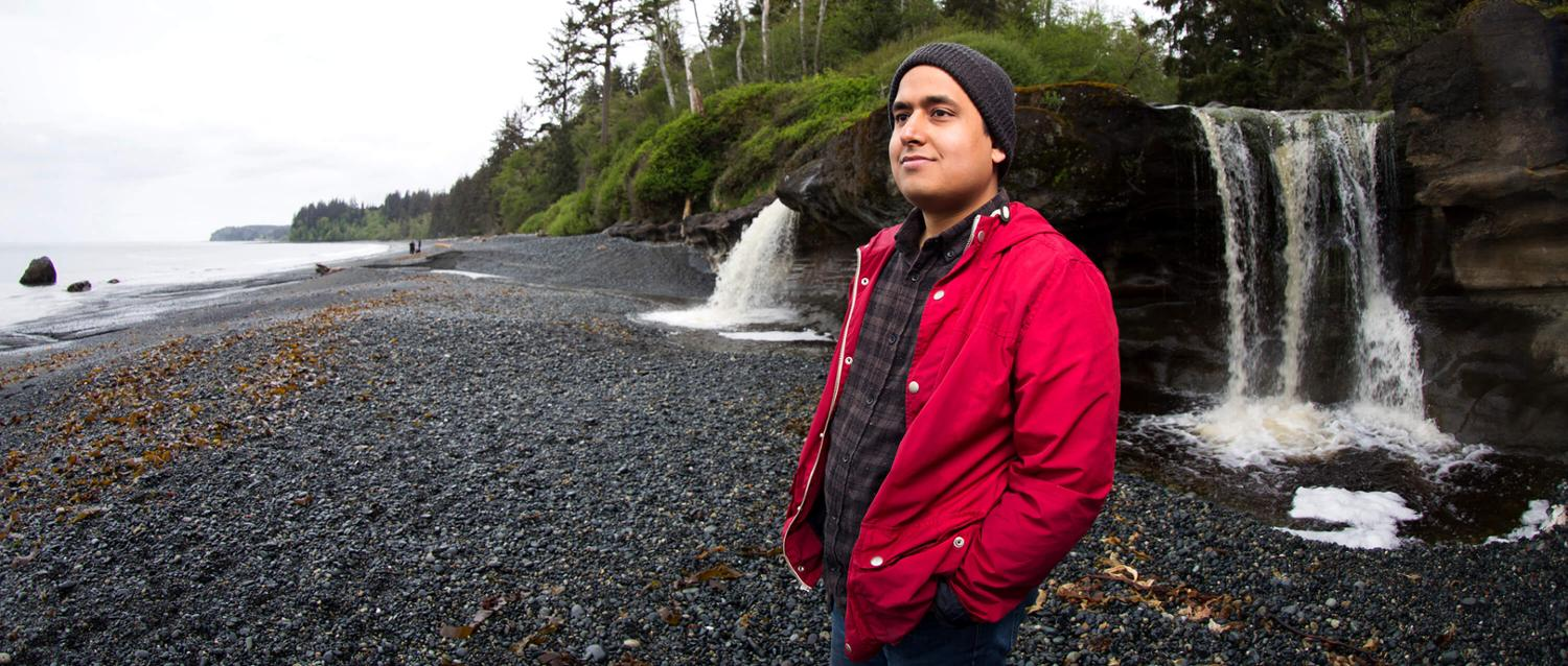 Devesh Bharadwaj on a West Coast beach in front of a waterfall