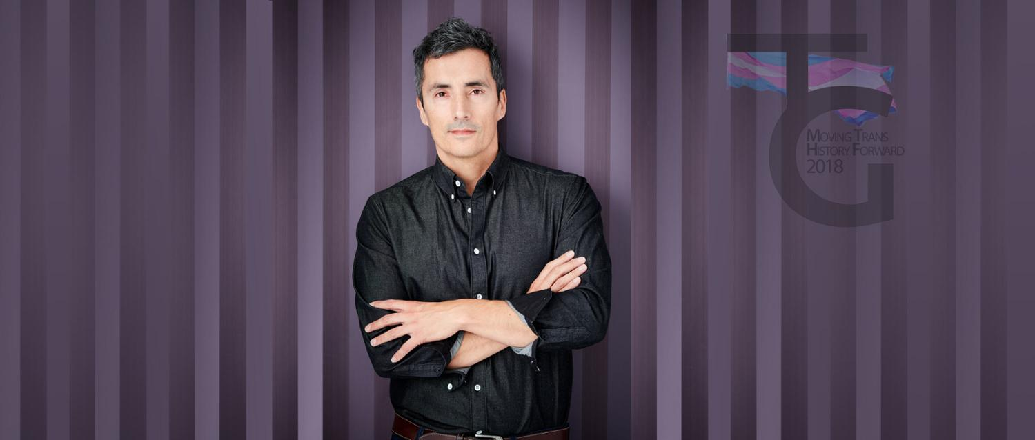 Two-Spirit artist Kent Monkman in front of a purple striped background