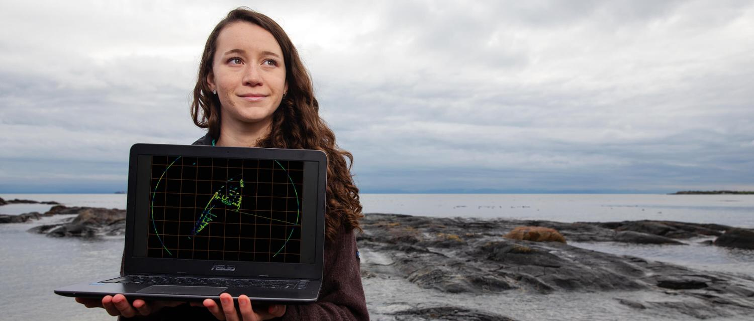 UVic student Desiree Bulger holding a laptop by the ocean