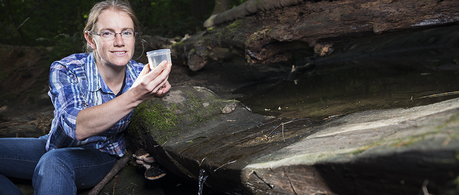 Buckley by a stream holding a cup of water