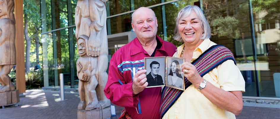 Mark and Fern Perkins holding old photos of themselves in front of UVic's First Peoples House