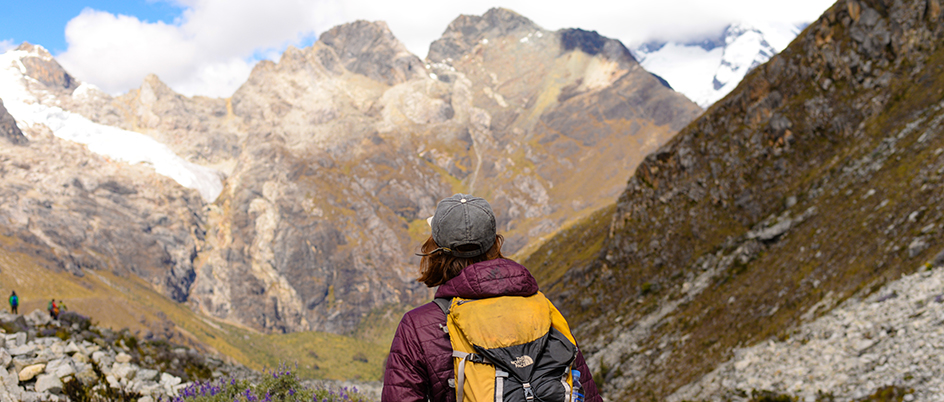 Student wearing a yellow backpack looking at the mountains of Peru
