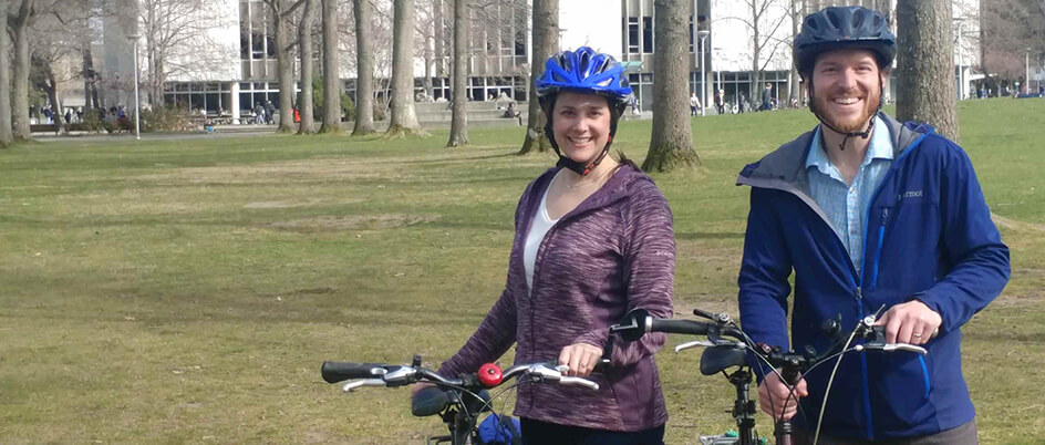 Matt Greeno and Susan Kerr hold their bikes on the quad