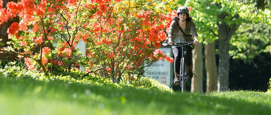 Person cycling on the UVic campus