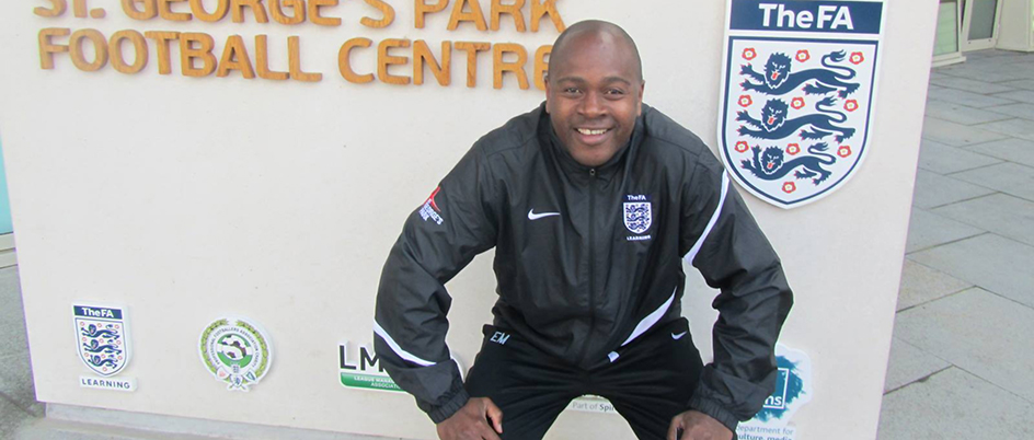 Eddie Mukahanana crouching by a St. George's Park Football Centre sign