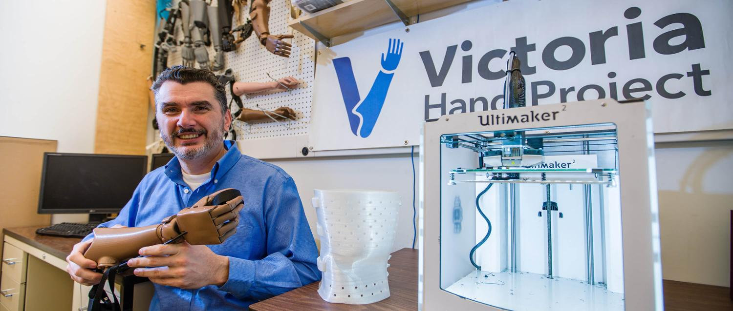 Nick Dechev holds an artificial hand in front of a Victoria Hand Project sign.
