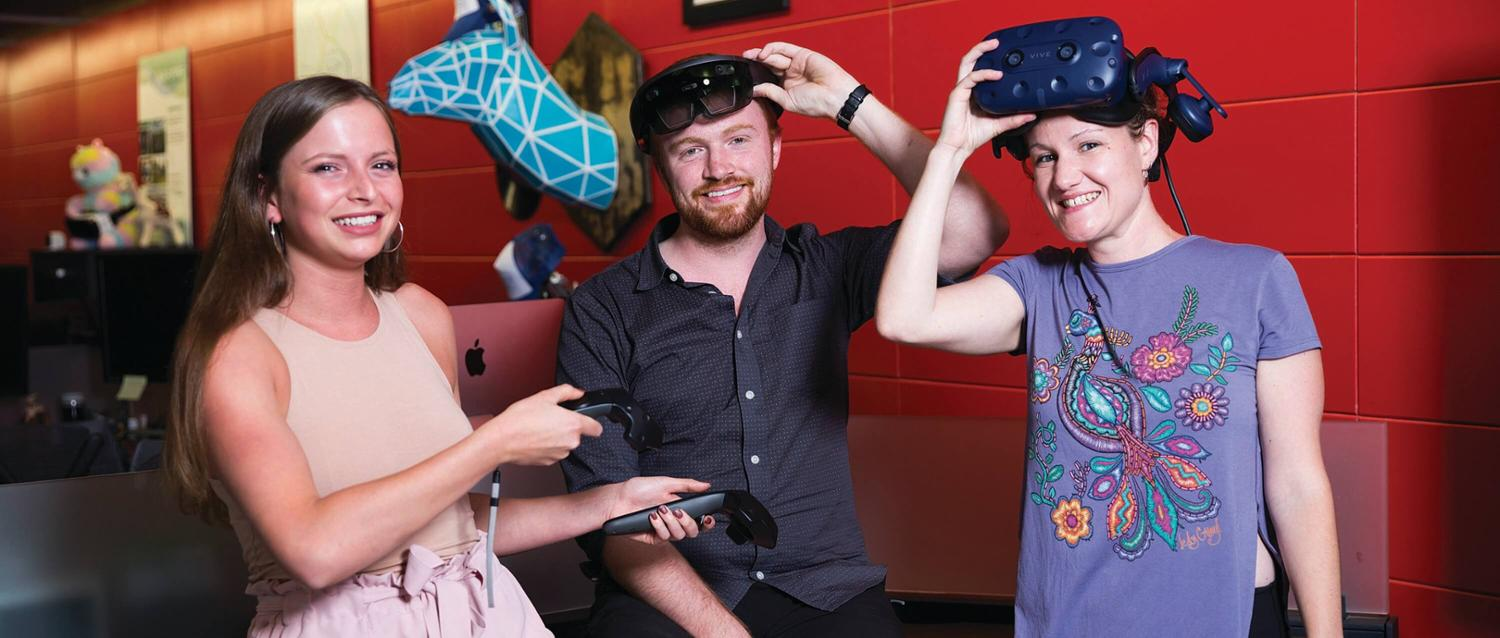 three students pose with virtual reality goggles
