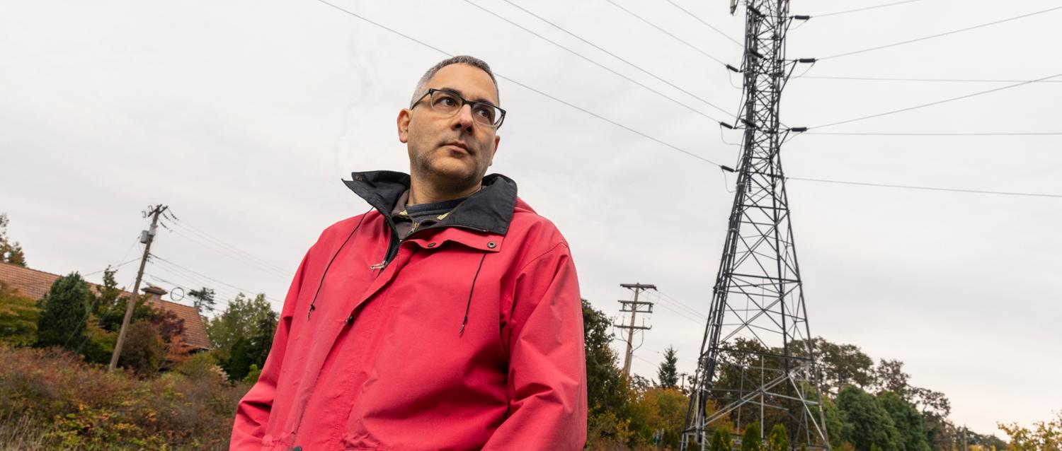 Dennis Hore poses in front of a power line in a field