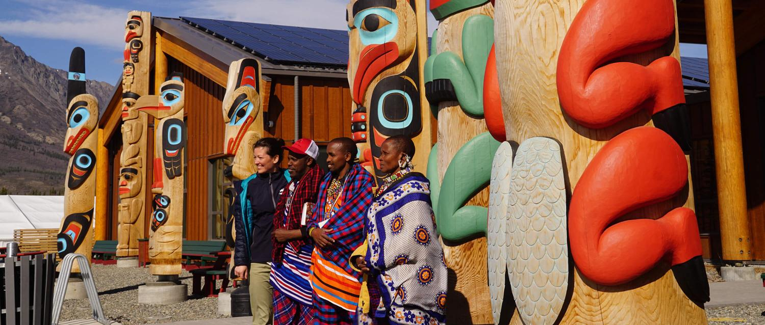 UVic geography faculty and three Maasai in front of totem poles