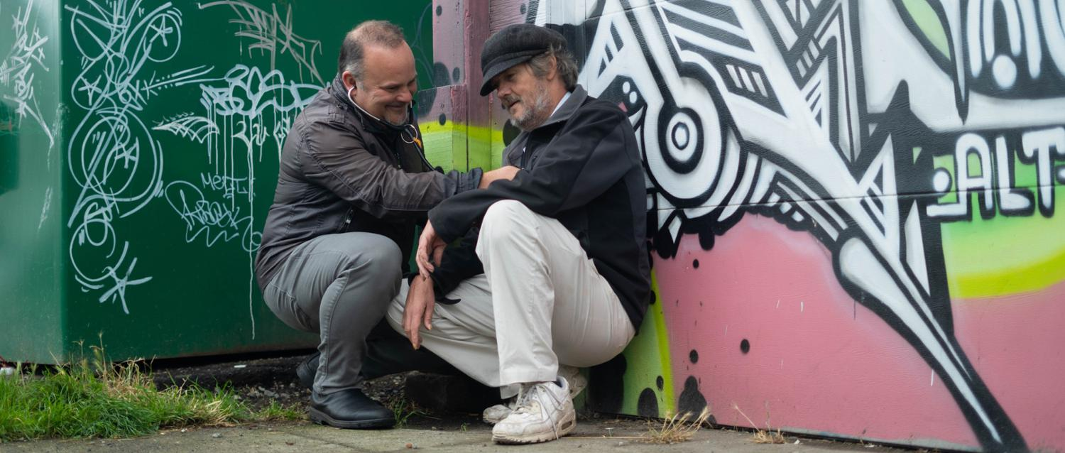 A physician crouches down to examine a patient who is sitting on a sidewalk against a wall.