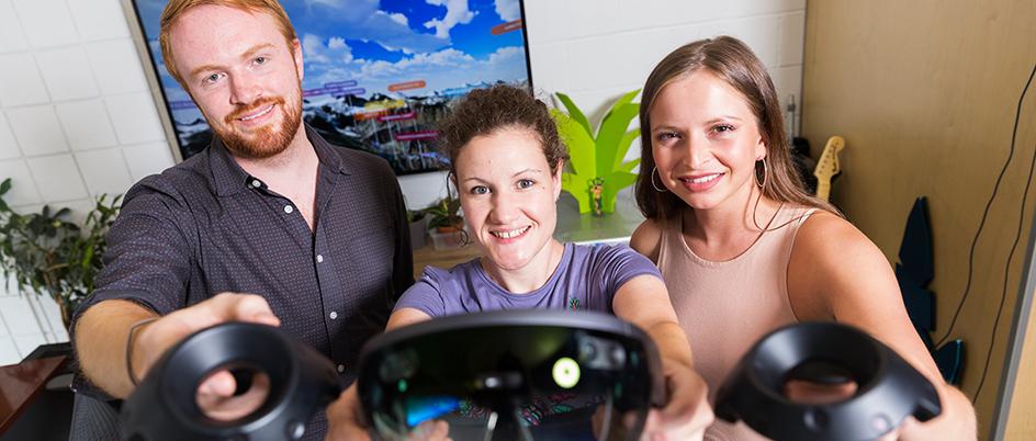 Three co-op students at LlamaZOO holding VR sets