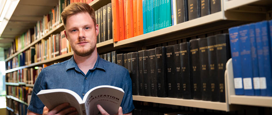 John Sakaluk poses with a large book open in front of a library shelf.