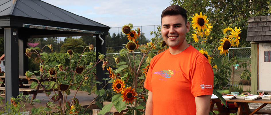 Peter Underwood poses in front of sunflowers with his orange t-shirt