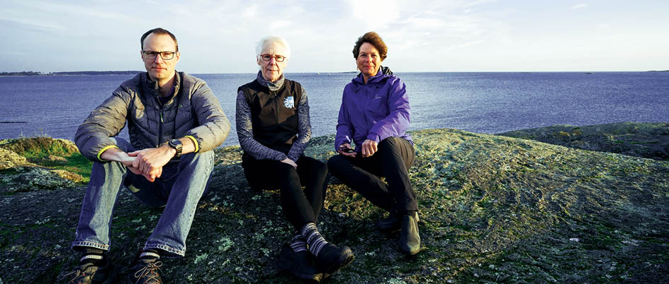 Crawford, Moran and Seitzinger sit on a rock with the ocean behind them.