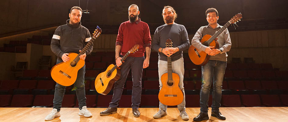 Members of the Orontes quartet pose on stage with their guitars