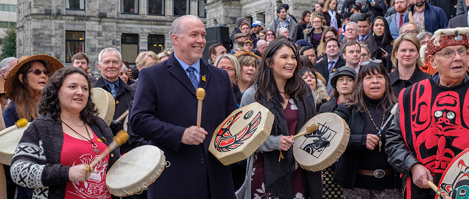 Sage in front of parliament buildings with John Horgan
