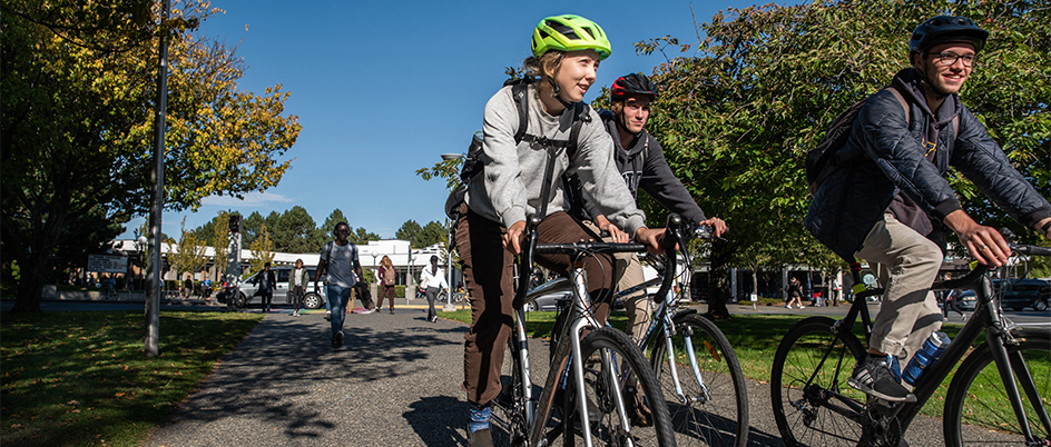 Three students bike across the UVic campus