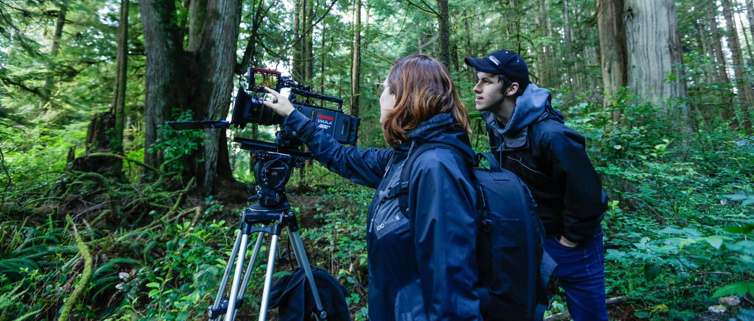 Kelly Richardson and student hold a video camera surrounded by forest.