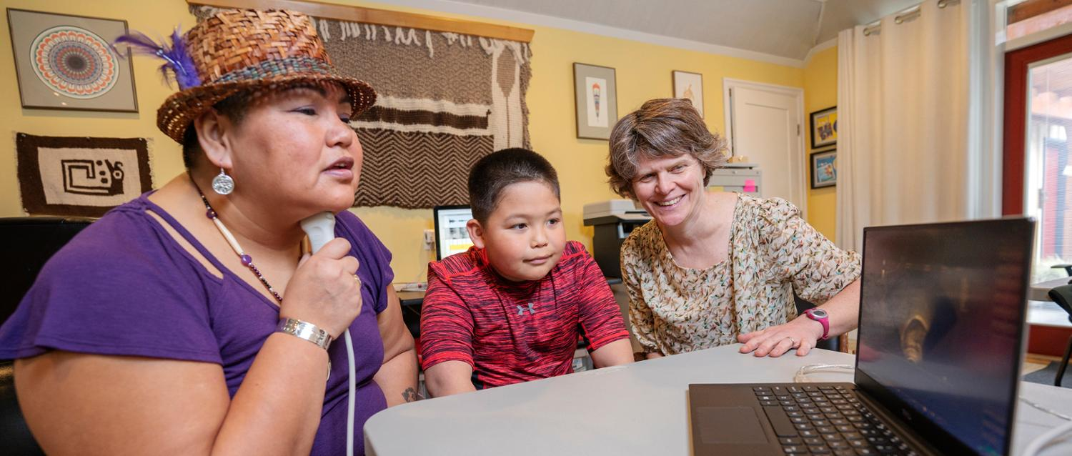 Agnes Violet Sharon Seymour practices her pronunciation using ultrasound technology with her son, Luke, and UVic linguist Sonya Bird.