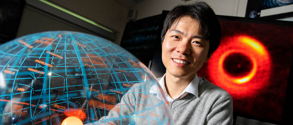 Dr. Duong poses with planetary disk model