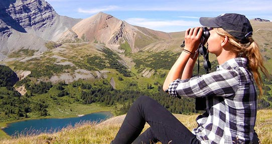 Student on a mountainside looking through binoculars
