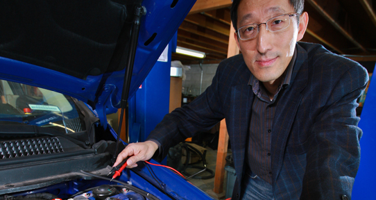 Researcher working on a car
