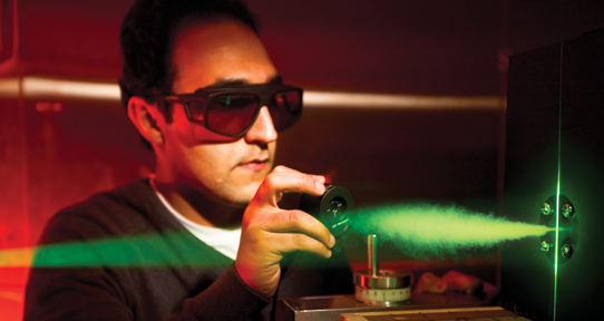 UVic male researcher in a lab working with green laser light fuel cell