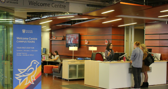 A UVic staff member helping visitors at the front desk of the Welcome Centre.