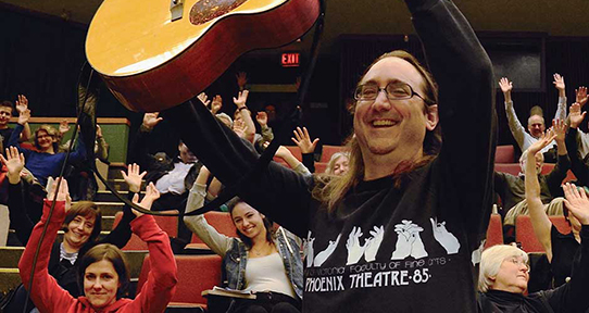 Mark Leiren-Young holding up a guitar during a lecture