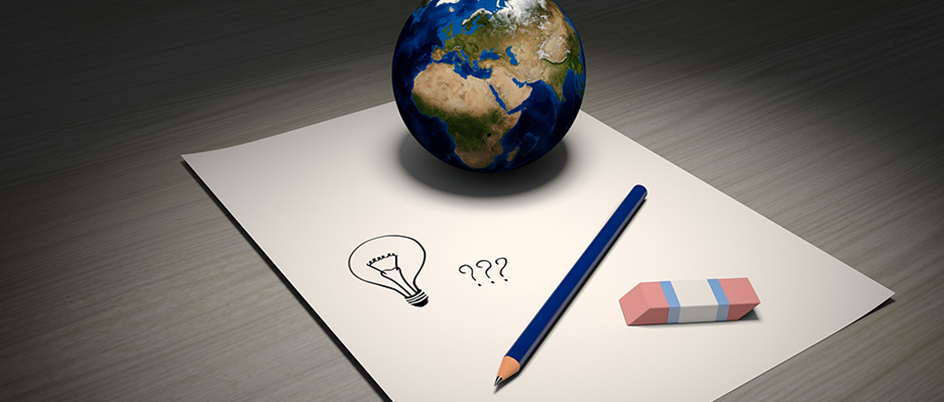 stock image of pencil, paper, and a small globe on a desk