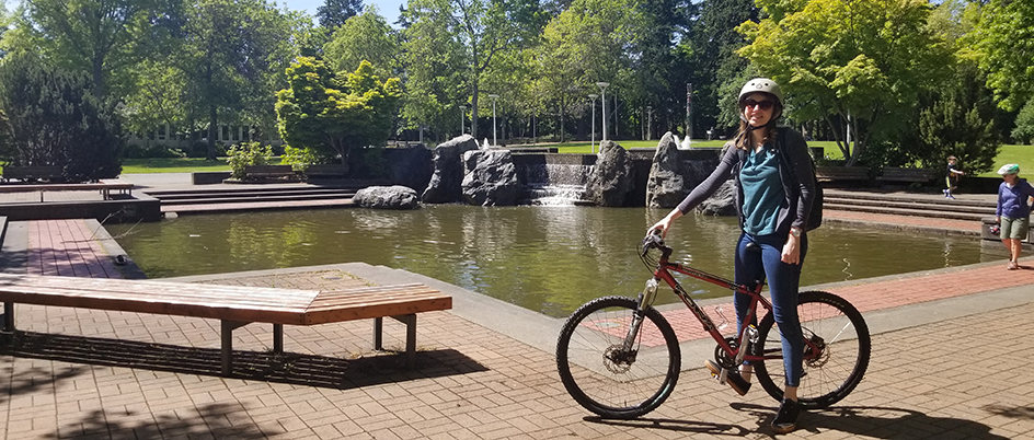 Isabelle Staiger standing with her bike in the UVic quad