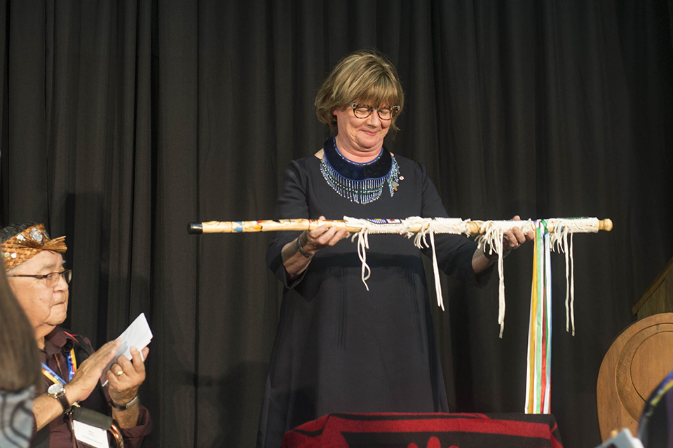 Shelagh Rogers on stage holding the Walking Stick
