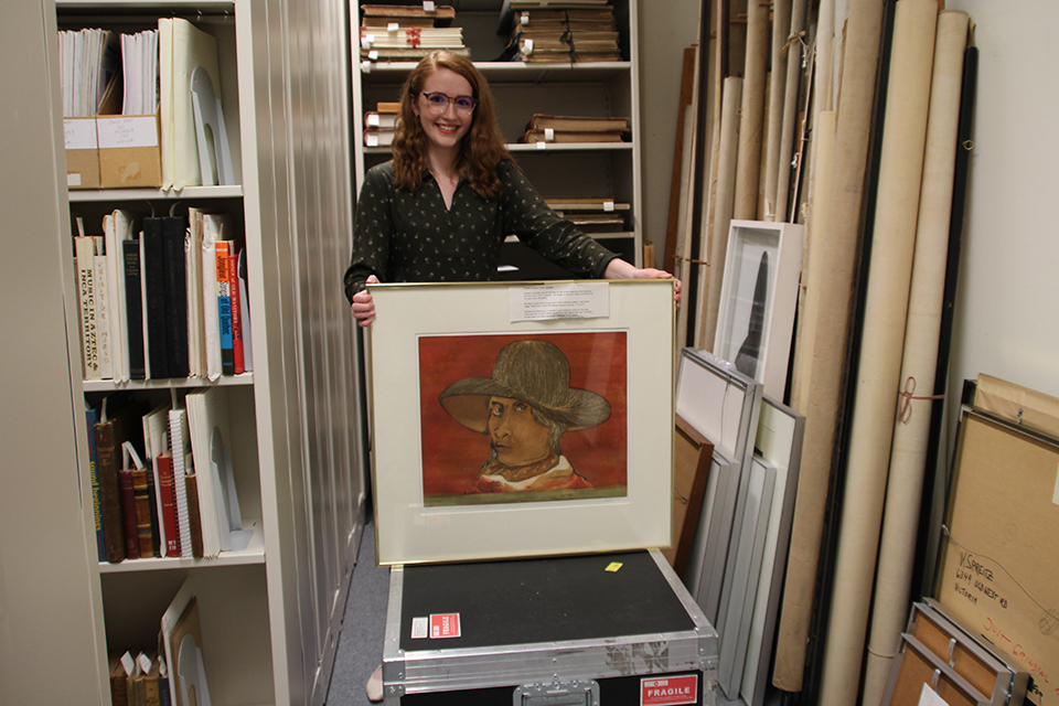 Greenhill holding up framed artwork in UVic Special Collections