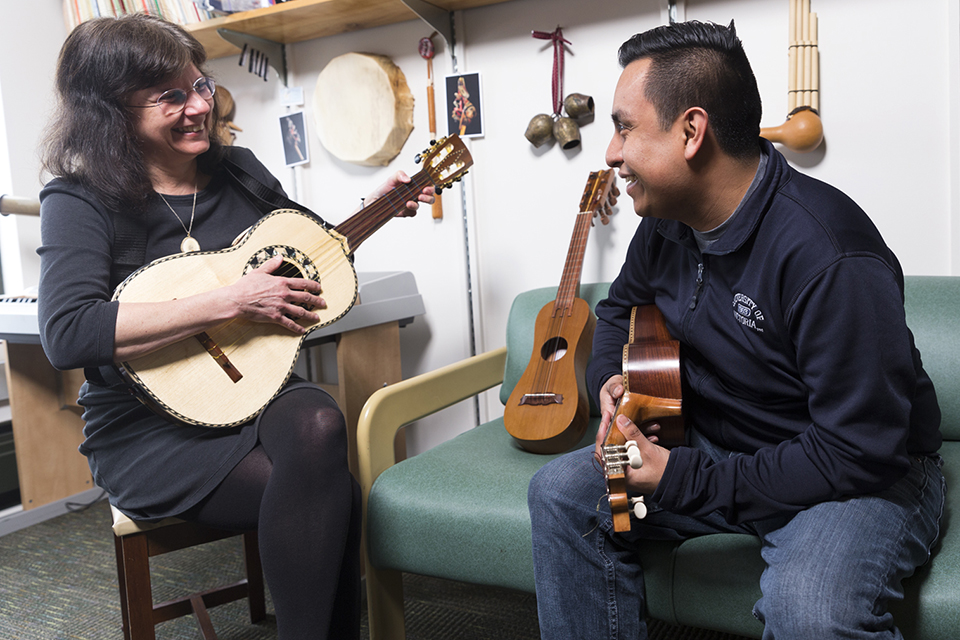 Anita Prest and Hector Vazquez Cordoba holding guitars in an office