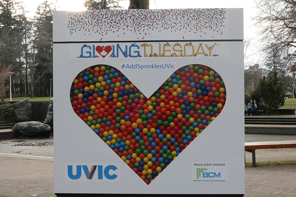 Large Giving Tuesday sign on campus with a colourful heart and sprinkles