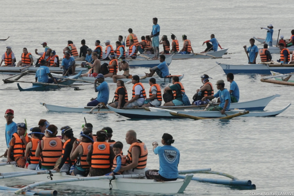 Several boats of people wearing lifejackets and looking for whalesharks