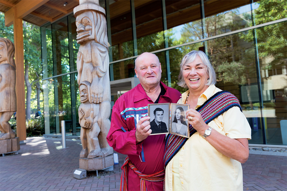Fern and Mark Perkins outside of UVic's First Peoples House holding old photos of themselves