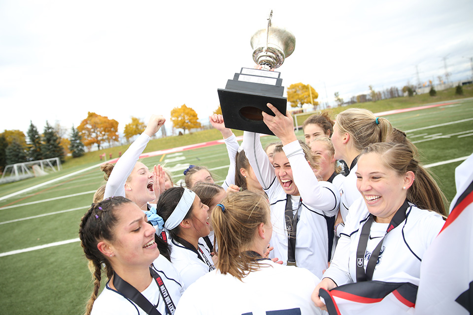 Vikes field hockey team cheering and hoisting the championship banner and cup