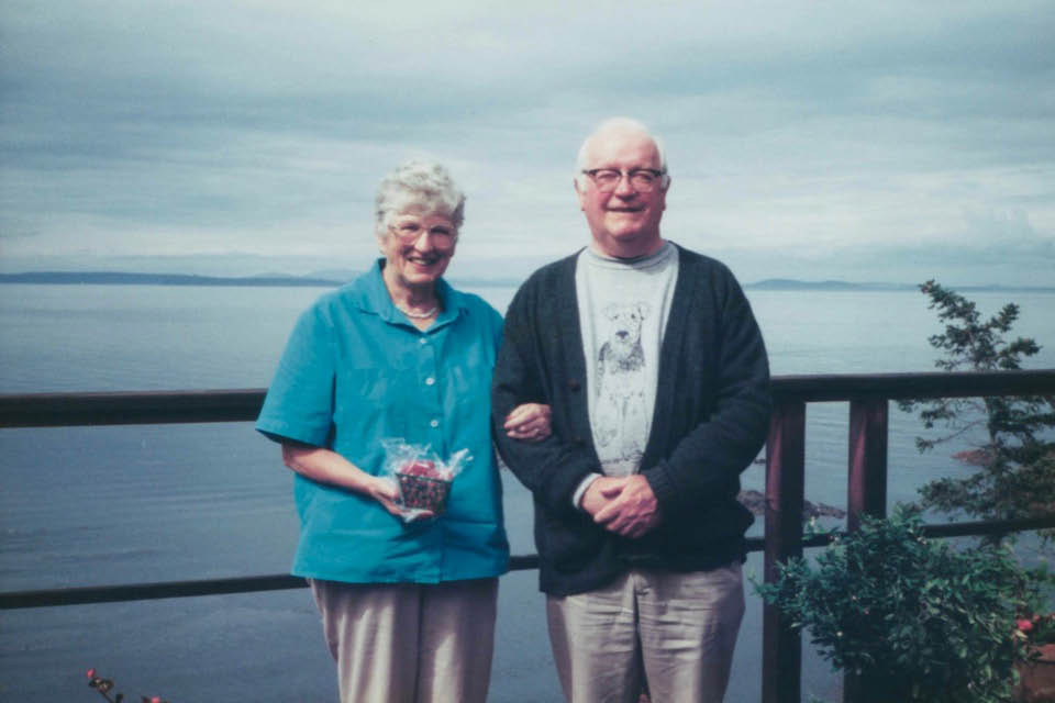 Alisa and Roger Bishop pose on a balcony overlooking an ocean view.