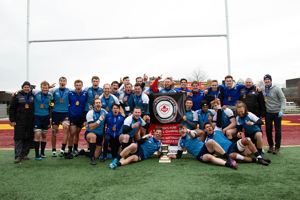 Vikes men's rugby team photo with winning trophy.