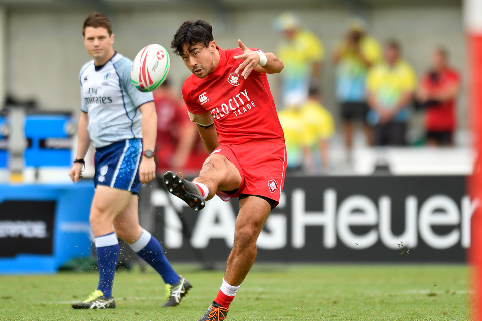 Nathan Hirayama kicks a rugby ball in an international tournament for Canada.
