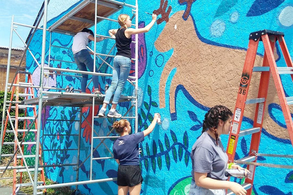 Students painting a mural outside