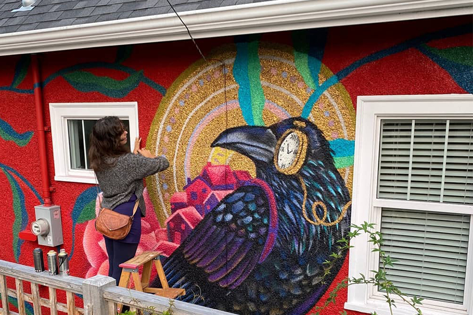 Gallivan painting a mural outside