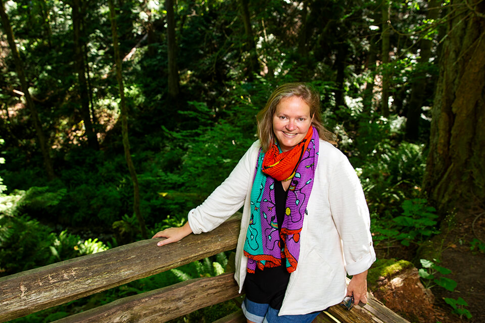 Heather Castleden stands in front of a green forested area, smiling.