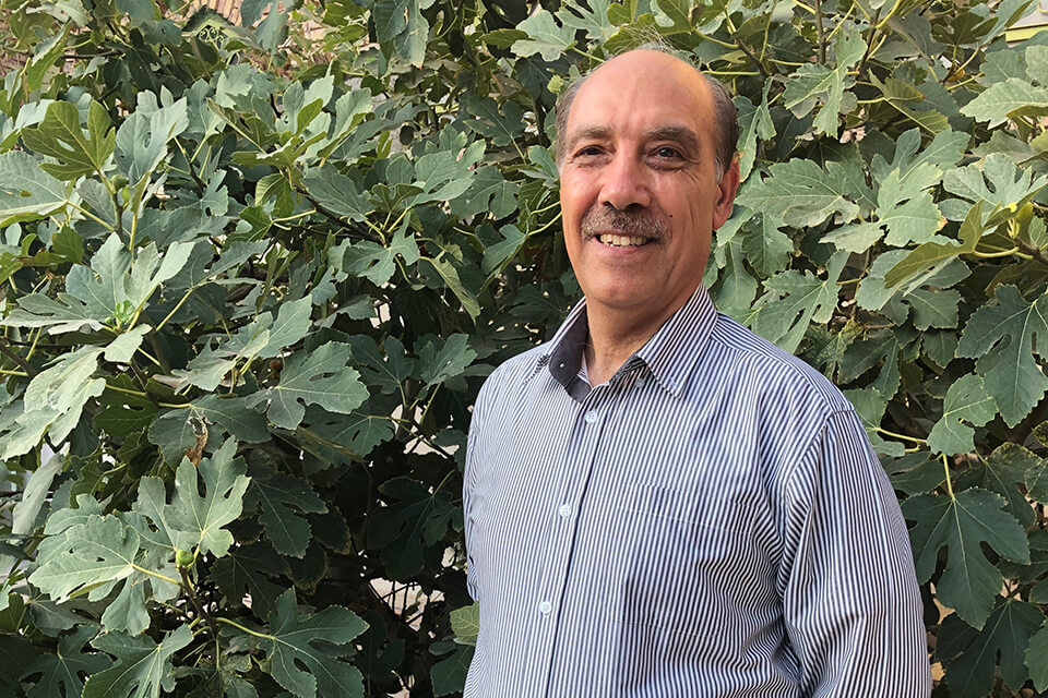 Hossein Nassaji stands in front of green leafy background, smiling.